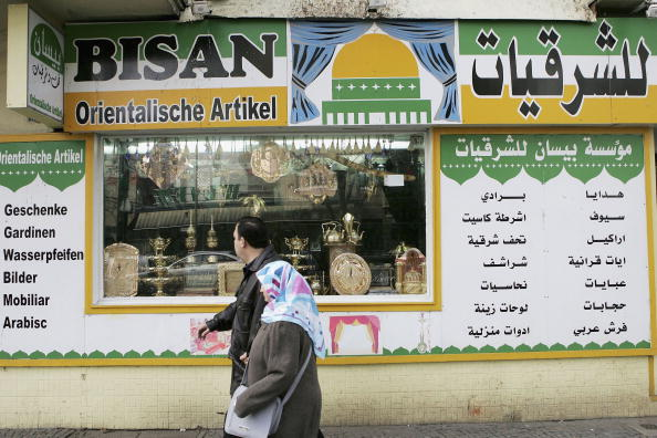 BERLIN - APRIL 3:  People walk past a store with signs written in Arabic April 3, 2006 in the Neukoelln district in Berlin, Germany. Reports of violence at a nearby high school have thrown the spotlight onto integration policies, with opposition parties claiming that current polcies are inadequate at integrating the many resident foreigners, many of whom are from Islamic or Eastern European countries, into German society. Europe is struggling to find an adequate solution to integration of immigrants, with many liberals warning of cultural imperialism should immigrants be forced to take on the values of their host countries, while many conservatives argue that newcomers must learn the language and accept the cultural values of their new homeland. (Photo by Sean Gallup/Getty Images)