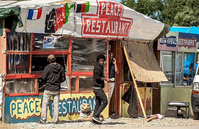 "Migrants walk in front of makeshift restaurants in the so-called 'Jungle' migrant camp in the French northern port city of Calais on August 12, 2016. A French judge on Friday rejected a bid by authorities in Calais to close unlicensed shops and eateries in the migrant camp. The authorities sought an emergency order to close 72 unlicensed stalls and restaurants dotted among the tents housing at least 4,500 migrants and asylum-seekers who are aiming to reach Britain. But in his ruling, the judge said that while the concerns expressed were ""completely understandable,"" the matter was not urgent enough to warrant the expulsion of the vendors. / AFP / PHILIPPE HUGUEN (Photo credit should read PHILIPPE HUGUEN/AFP/Getty Images)"