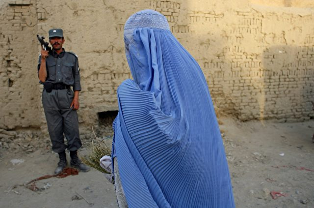 KABUL, AFGHANISTAN - AUGUST 18:  A woman in a burqa walks by as Afghan police search a section of Kabul after a German woman was kidnapped from a restaurant on August 18, 2007 in Kabul, Afghanistan. Armed men kidnapped the woman, who worked for a small Christian organization called Ora International, and was with her boyfriend inside the restaurant eating lunch. Today's kidnapping comes after two Germans were taken hostage in separate incidients last month in central Afghanistan. In addition, a Taliban spokesman said today negotiations over 19 South Korean hostages has failed.  (Photo Paula Bronstein/Getty Images)