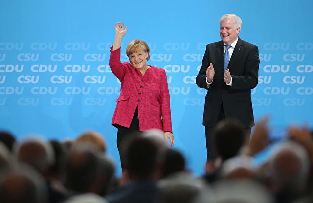 BERLIN, GERMANY - JUNE 24:  German Chancellor and German Christian Democratic Union (CDU) Chairwoman Angela Merkel and Bavarian Christian Social Union (CSU) Chairman Horst Seehofer receive applause after speaking at a summit of the two parties to present their election policy program on June 24, 2013 in Berlin, Germany. The two parties are in an alliance as the German Christian Democrats and currently lead in polls ahead of federal elections scheduled for September.  (Photo by Sean Gallup/Getty Images)