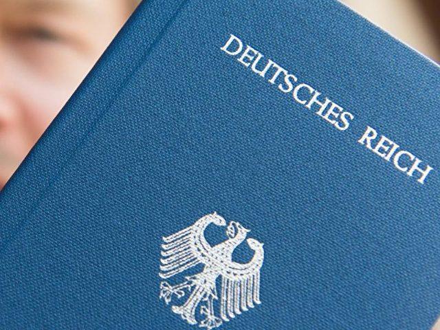 Ein Mann posiert mit seinem «Deutsches Reich Reisepass» für den Fotografen. Foto: Patrick Seeger/Illustration/dpa
