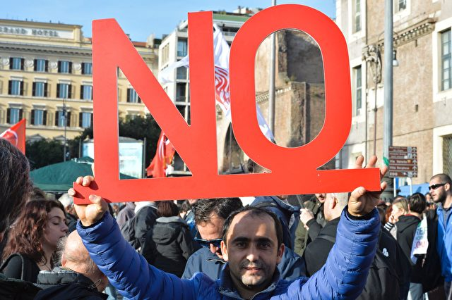 "A demonstrator holds a placard reading ""no"" during a demonstration of the ""C'e chi dice no"" (some say no) movement calling for a ""no"" vote to the upcoming referendum on constitutional reform in central Rome, on November 27, 2016.  Italy will hold a referendum on constitutional reform on December 4 in which Renzi has staked his political future on winning approval of a move to streamline parliament by replacing the Senate with a smaller, less powerful second chamber. / AFP        (Photo credit should read /AFP/Getty Images)"