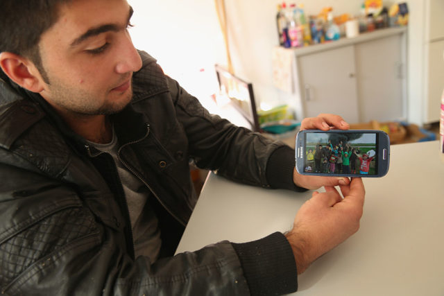 LETSCHIN, GERMANY - OCTOBER 09:  Kurdish Syrian asylum-applicant Mohamed Ali Hussein, 19, shows a visitor photos of his family in syria on his smartphone in the room he shares with his cousin Sinjar Hussein at the asylum-applicants' shelter that is their home in Vossberg village on October 9, 2015 in Letschin, Germany. The cousins arrived in Germany via Romania and the Balkans, though because Romanian authorities initially registered and fingerprinted them there, Mohamed and Sinjar have sought legal help from lawyers in Berlin in order to be allowed to apply for asylum in Germany. The cousins told of bad experiences in Romania, where they said police beat them. Approximately 60 asylum-seekers, mostly from Syria, Chechnya and Somalia, live at the Vossberg shelter, which is run by the Arbeiter-Samariter Bund (ASB) charity. Vossberg village is located in rural eastern Germany close to the border to Poland, and unlike shelters in southeastern Germany, it has experienced no incidents of right-wing animosity from locals, something an ASB spokesman attributes to strong cooperation between the municipality, schools and citizens' groups and an effective information campaign to educate locals about the newcomers. Germany has been inundated with hundreds of thousands of asylum applicants this year and is struggling to accommodate them.  (Photo by Sean Gallup/Getty Images)