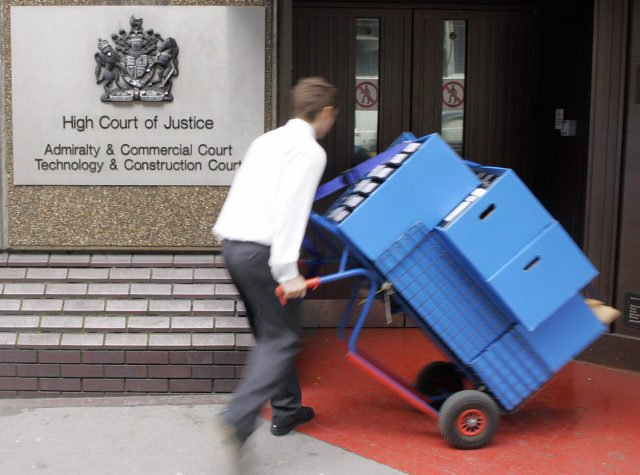 LONDON, United Kingdom: Legal documents are delivered to the Technology and Construction Court at the High Court in London, 25 April 2006, on the first day of a legal battle between Australian construction giant Multiplex and Cleveland Bridge UK Ltd. (CBUK) over the delay-dogged Wembley Stadium project. Multiplex is seeking up to 45 million pounds (65 million euros, 80 million dollars) while Cleveland Bridge, which made the 757-million-pound, 90,000-seat stadium's 134-metre (440-foot) arch, is counter-claiming 25 million pounds. Wembley had been due to host the showpiece FA Cup final on May 13 but delays, defects and disputes have forced the English Football Association governing body to switch the tie to Cardiff's Millennium Stadium. AFP PHOTO/LEON NEAL (Photo credit should read Leon Neal/AFP/Getty Images)