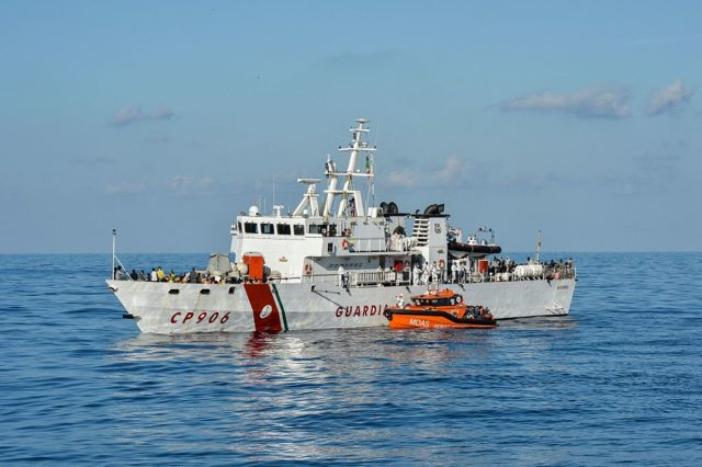 """Migrants and refugees are transferred from the Topaz Responder, a ship run by Maltese NGO """"Moas"""" and the Italian Red Cross, to the Italian Coast Guards ship CP906, on November 4, 2016, after rescue operations off the Libyan coast in the Mediterranean sea. Around 750 migrants were rescued across the Mediterranean on November 3, 2016 by the Italian coast guard, a Frontex ship, a Save The Children vessel, German NGO Jugend Rettet's Iuventa and two boats run by the Malta-based MOAS (Migrant Offshore Aid Station). But at least 110 migrants are feared drowned after they were forced at gunpoint to set sail from Libya, while many more may have died in a separate shipwreck, survivors said. / AFP / ANDREAS SOLARO        (Photo credit should read ANDREAS SOLARO/AFP/Getty Images)"""