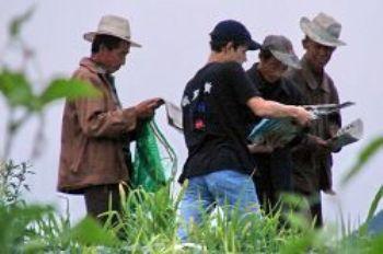 Добровольцы из России распространяют «Девять комментариев» на полях и помогают людям выходить из рядов КПК. Фото: minghui.ca