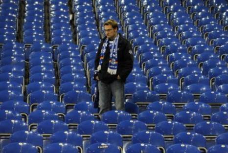 Одинокий болельщик «Шальке» на опустевшем после матча стадионе. Вельтинс Арена, Гельзенкирхен, Германия. Матч 1/4 финала Лиги чемпионов между «Шальке 04» и «Барселоной». Фото: JOHN MACDOUGALL/AFP/Getty Images