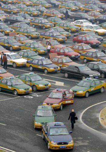 Женщина прогуливается вдоль вереницы стоящих такси. Фото: Liu Jin/AFP/Getty Images