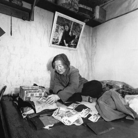 Неграмотная женщина раскладывает денежные купюры по размеру и рисункам. Зима 2001 года. Провинция Хэйлунцзян. Фото: Zhan Zheng