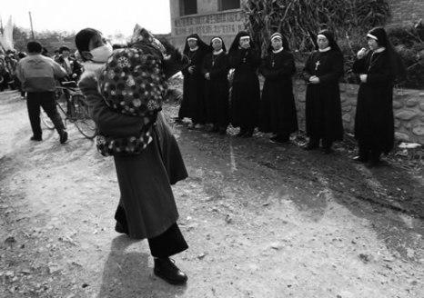 Молодая мама с ребёнком на руках проходит мимо группы монашек. Провинция Шэньси. 1995 год. Фото: Hu Wugong