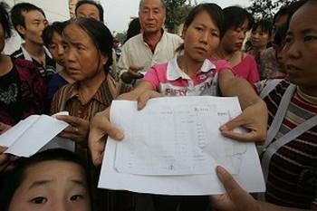 Родители пострадавших детей держат заключения врачей, подтверждающие отравление свинцом. Фото с epochtimes.com