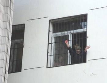 Пэн Юнкан через зарешёченное окно психиатрической больнице машет своим друзьям рукой и просит, чтобы они забрали её оттуда. Фото: Civil Rights & Livelihood Watch