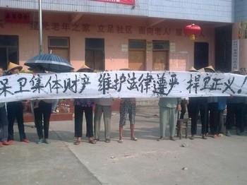 Крестьяне деревни Байхутоу держат плакат с надписью: «Защитим коллективную собственность, защитим авторитет закона, защитим справедливость». Фото предоставлено крестьянами