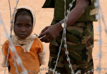 Девочка смотрит сквозь колючую проволоку на суданскую базу миссии Африканского Союза, расположенной в Лабардо в южном Дарфуре. Фото:  Stuart Price/AFP/Getty Images