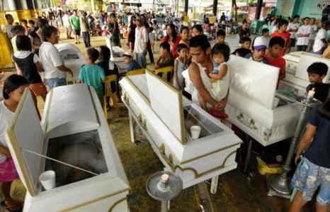 Родственники около гробов жертв урагана Кетсан в Маниле (28.09.2009).  Фото: JAY DIRECTO/AFP/Getty Images