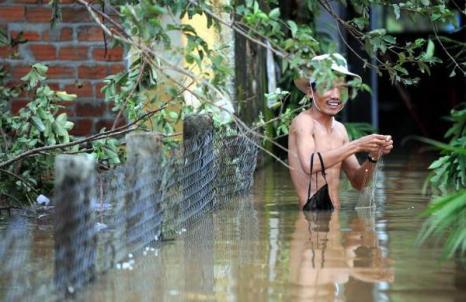 Мужчина вылавливает свои вещи в центре провинции Куан Нам во Вьетнаме (30.09.2009) Фото: HOANG DINH NAM/AFP/Getty Images