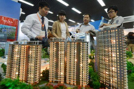 Люди рассматривают продаваемую недвижимость на модели микрорайона Пекина, Инвестиционная выставка, 20 сентября 2012 года. Фото: MARK RALSTON/AFP/GettyImages
