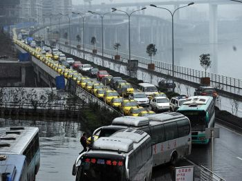 Такси, стоящие в очереди на заправку в г. Чунцин, юго-запад Китая, 18 ноября 2009 г. Таксисты объявили забастовку в начале ноября в знак протеста против дефицита топлива и конкуренции со стороны нелицензированных такси и по ряду других вопросов. Забастовка водителей стала одной из целей Бо Силая в рамках кампании «Удар по мафии». Фото: AFP / Getty Images