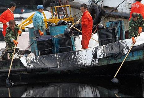 После аварии на нефтепроводе специальные бригады выбирают из вод Жёлтого моря вытекшую нефть. Фото AP Photo