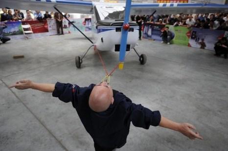 Дон Чжаншень тащит самолёт, привязанный к его векам. Фото с epochtimes.com