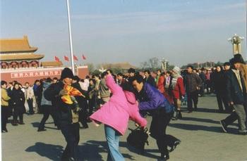 Полицейские агенты арестовывают сторонницу Фалуньгун, которая вышла на пекинскую площадь Тяньаньмэнь выразить протест против репрессий её единомышленников со стороны правительства. Фото с epochtimes.com
