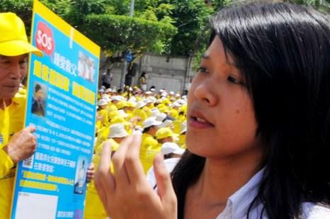 Чжун Ай, дочь Чжун Динбана из Тайваня, арестованного в Китае в июне, на фоне сотен последователей Фалуньгун, медитирующих во время акции в поддержку Чжуна в центре Тайбэя, 23 июля 2012 года. Фото: Mandy Cheng/AFP/Getty Images
