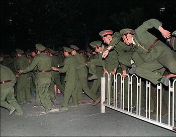 Солдаты Народно-освободительной армии перепрыгивают через барьер на площади Тянь-Ань-Мэнь в центре Пекина во время кровавого подавления студенческого движения 4 июня 1989 г. Фото: Thomas Cheng/AFP/Getty Images