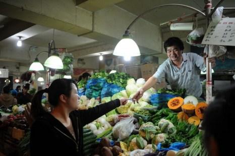 Торговец продаёт овощи на рынке в Шанхае, 18 октября 2012 года. Фото: Peter Parks/AFP/Getty Images