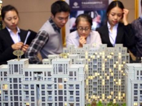 Потенциальные покупатели разглядывают модель роскошного жилого района. Фото: AFP/Getty Images