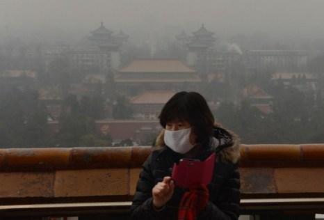 Китайский турист пытается в смоге сфотографировать исторический парк Цзиншань, Пекин, 31 января 2013 года. Фото: Mark Ralston/AFP/Getty Images