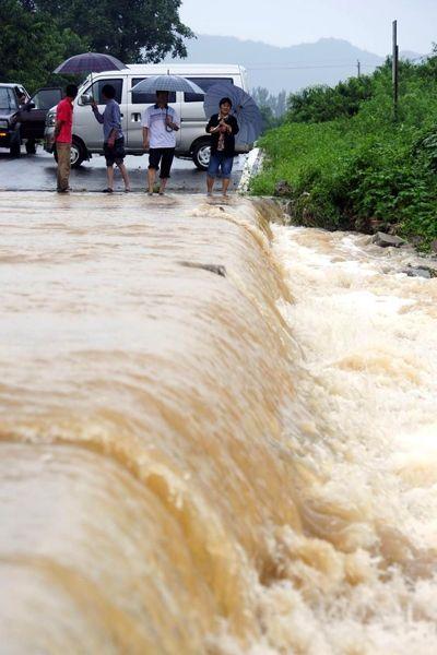 Разрушенная горная дорога, люди переправляются по воде. Фото: kanzhongguo.com