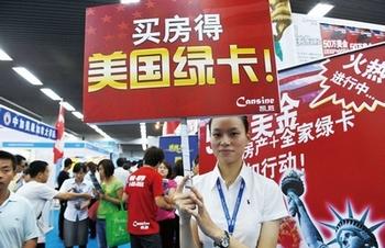 """Надпись на табличке: «Купи дом, получи """"зелёную карту"""" США». Пекин. 2010 год. Фото: AFP"""