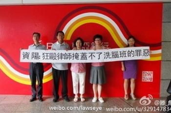 Пятеро адвокатов держат плакат с надписью: «Цзыян, безумное избиение адвокатов не поможет скрыть злодеяния, совершаемые в классе промывания мозгов!». Май 2013 года. Фото с epochtimes.com