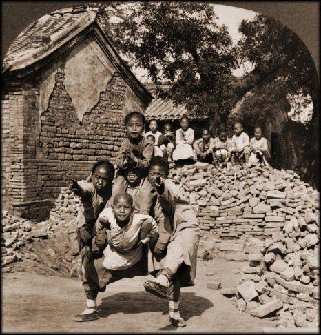 Бездомные дети выступают на улице, изображая голову дракона. Пекин. 1902 год. Фото с kanzhongguo.com