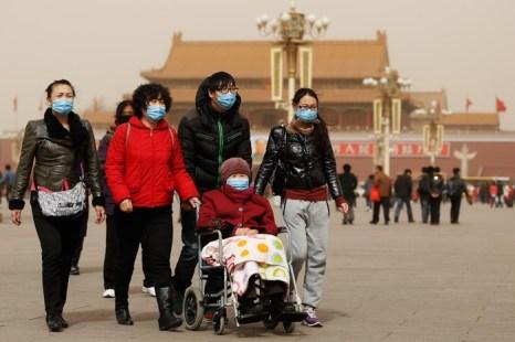 Люди в Пекине закрываются от песчаной бури масками 9 марта 2013 г. Фото: Feng Li/Getty Images