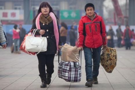 Люди с большими сумками едут домой. 27 января 2013 года, железнодорожный вокзал Пекина. Фото: Ed Jones/AFP/Getty Images