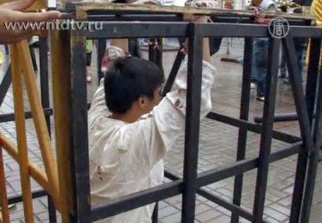Ли во время инсценировки одного из видов пыток, которым в Китае подвергают сторонников Фалуньгун. Киев. Украина. Фото: NTD TV