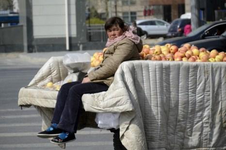 Торговка яблоками в Пекине, 14 апреля 2013 года. Уличных торговцев преследуют специальные службы, нанимаемые властями для обеспечения муниципальных нормативных актов. Фото: Wang Zhao/AFP/Getty Images