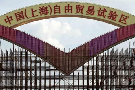 Рабочие трудятся над созданием большого плаката «Китай (Шанхай), пилотная зона свободной торговли» на воротах зоны свободной торговли Вайгаоцяо в Шанхае, 23 сентября 2013 года. Фото: STR/AFP/Getty Images