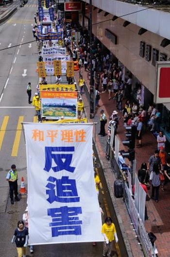 На баннере слова «мир и разум» (оранжевые иероглифы) и «прекратить преследования [Фалуньгун]» (синие иероглифы), 23 июня 2013 года, Гонконг. Фото: Song Xianglong/Epoch Times