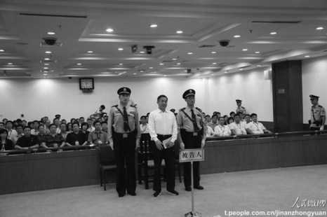 Бо Силай стоит между двумя офицерами во время суда в воскресенье в Цзинане, провинция Шаньдун. Он был приговорён к пожизненному заключению. Фото: Weibo.com