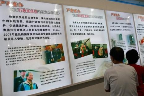 Посетители выставки смотрят на плакат с изображением якобы коррумпированных членов коммунистической партии Китая, Пекин, 2 сентября 2007 года. Фото: Teh Eng Koon/AFP/Getty Images