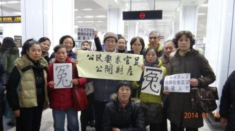 Протестующие держат плакаты в Экспоцентре в Шанхае, где проходит ежегодная парламентская сессия. 19 января 2014 г. Фото предоставлено апеллянтами