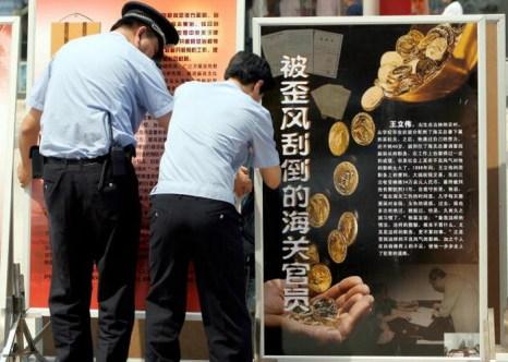 Китайские полицейские развешивают антикоррупционные плакаты в центре Пекина, 11 июня 2007 года. Фото: Teh Eng Koon/AFP/Getty Images