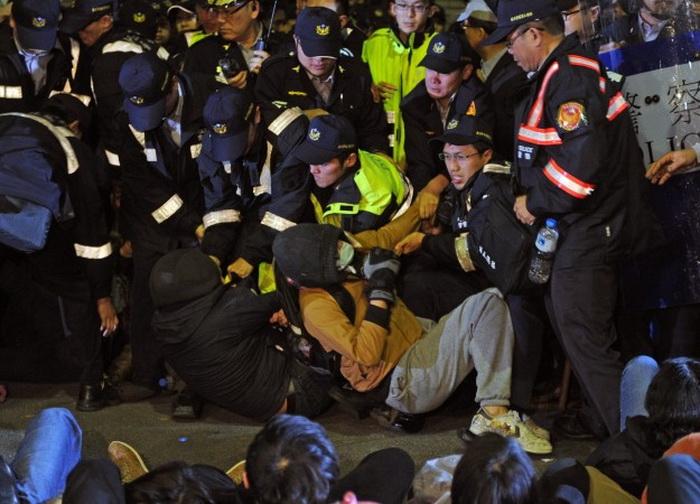 Полиция пытается поднять и оттащить студентов от здания Законодательного Юаня в Тайбэе в ночь на 24 марта 2014 года. В столкновении ранены десятки студентов. Фото: SAM YEH/AFP/Getty Images