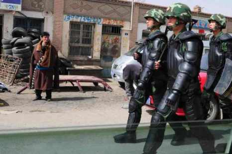 Тибетец в традиционной одежде наблюдает за китайскими военными, шагающими по улицам Гомаин на Тибетском плато. Китайская политика направлена на замену этнических языков наречием «мандарин». Фото: Frederic J. Brown/AFP/Getty Images