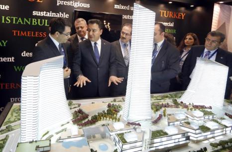 Турецкий вице-премьер-министр Али Бабаджан (2-Л) смотрит на масштабную модель «Метрополь Стамбула, Турция» на инвестиционной выставке MIPIM-2013. Фото:  VALERY HACHE/AFP/Getty Images