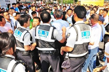 Обвиняемый Цуй пытается напасть на сотрудников правопорядка. Фото: Guohuan Jin/The Epoch Times