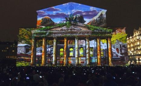 Зрители смотрят на световое шоу, отображающееся на фасаде Большого театра, во время третьего Московского международного фестиваля «Круг света» в Москве, 4 октября 2013 года. Фото: IVAN NOVIKOV/AFP/Getty Images