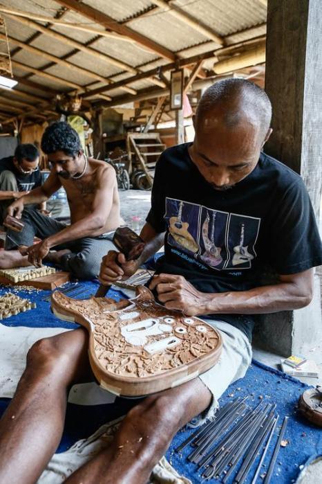 Индонезийские мастера производят гитары Blueberry с уникальной ручной резьбой на индонезийском острове Бали, которые имеют спрос по всему миру. Художники мастерской провели семинар 11 октября 2013 года. Фото: Putu Sayoga/Getty Images